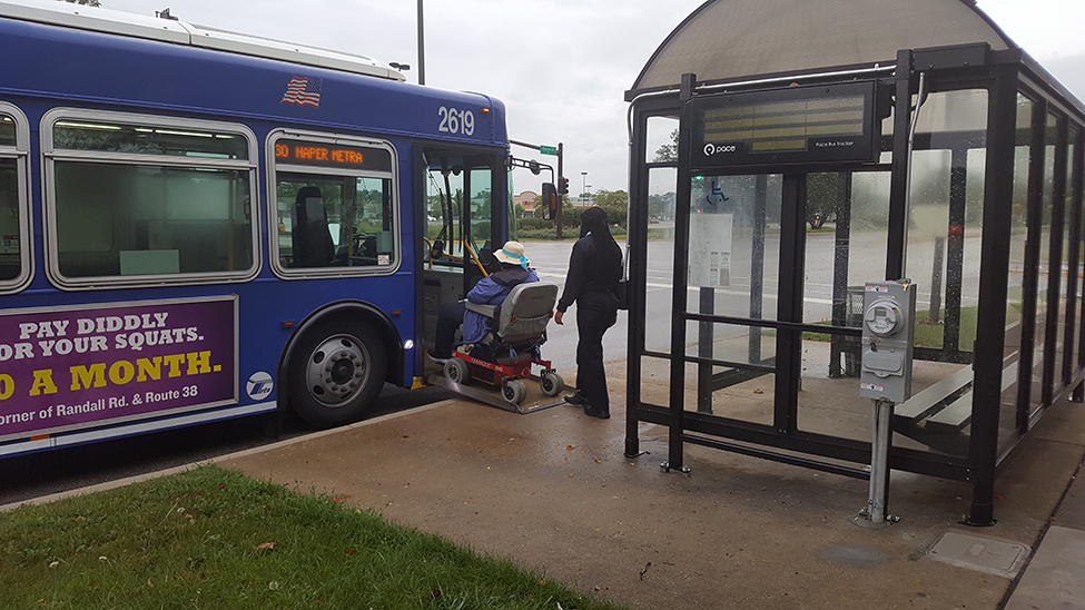 driver helps wheelchair user up ramp into bus