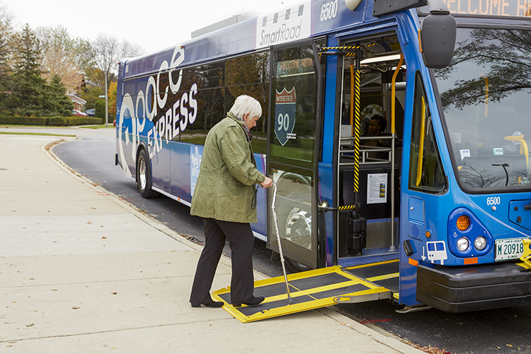 Woman with cane using ramp to board bus