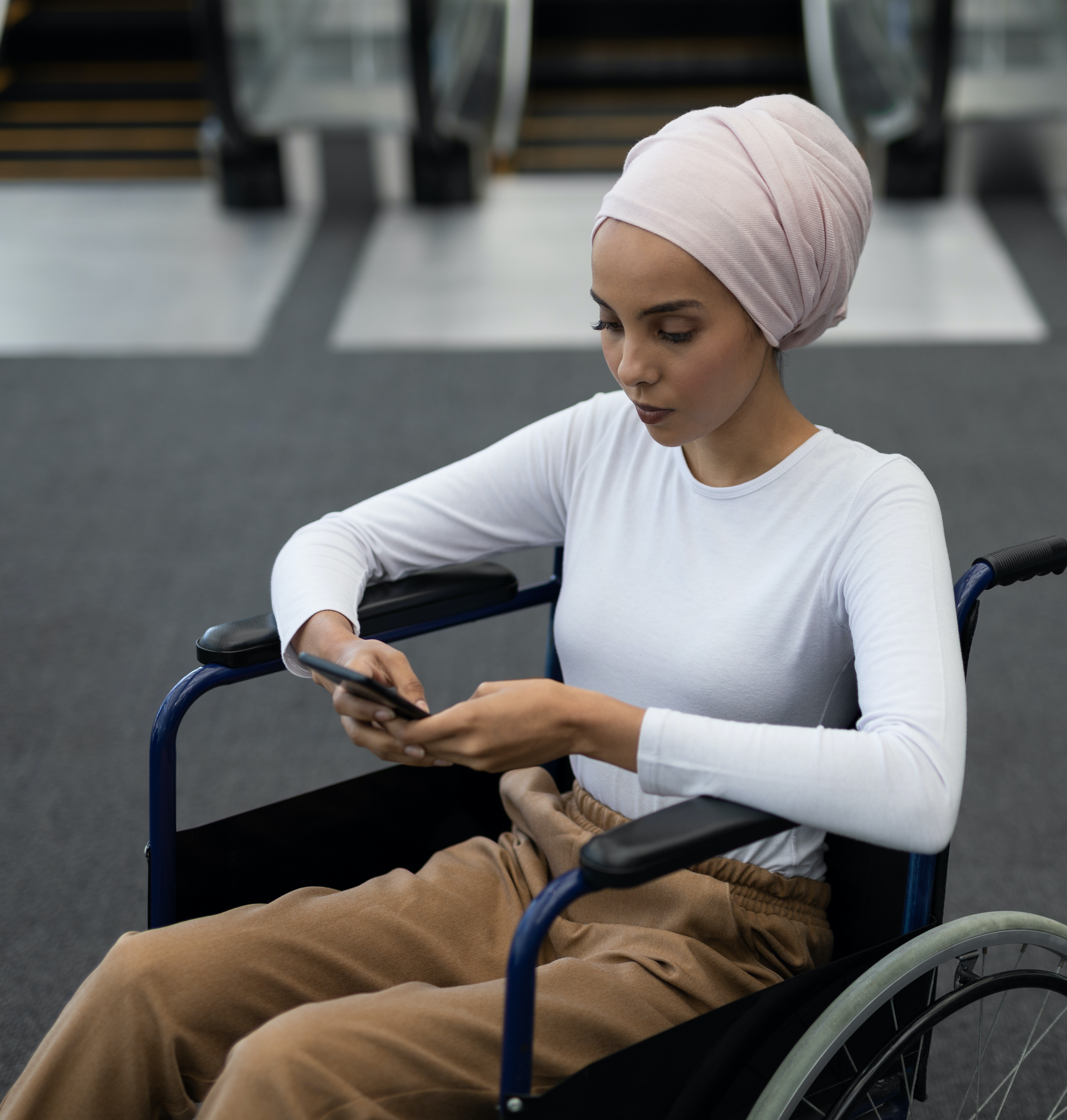 Woman in wheelchair checking phone