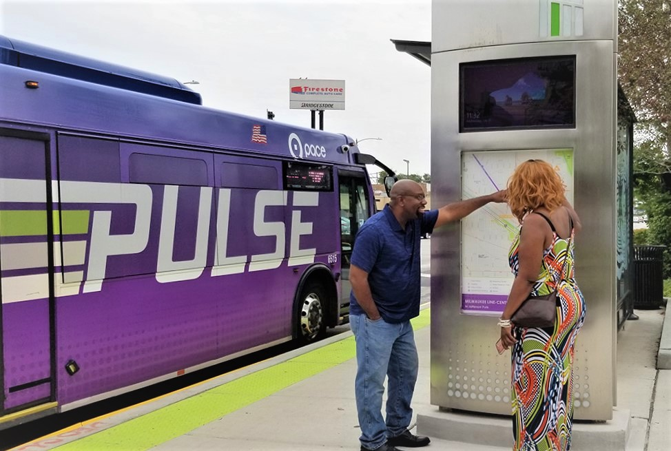 Image of Pulse station with riders checking the map on a vertical marker